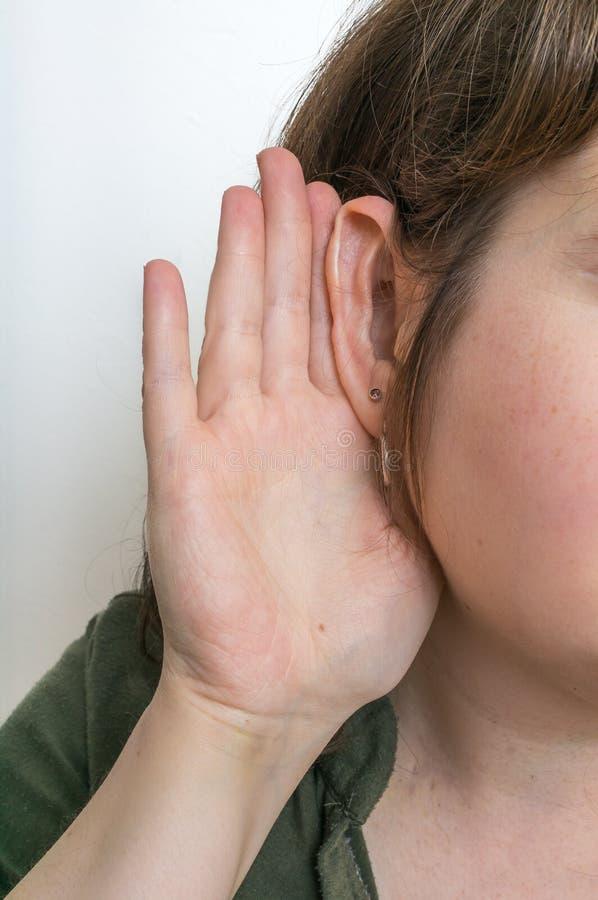 La femme tient sa main près de l'oreille et de l'écoute soigneusement photographie stock libre de droits