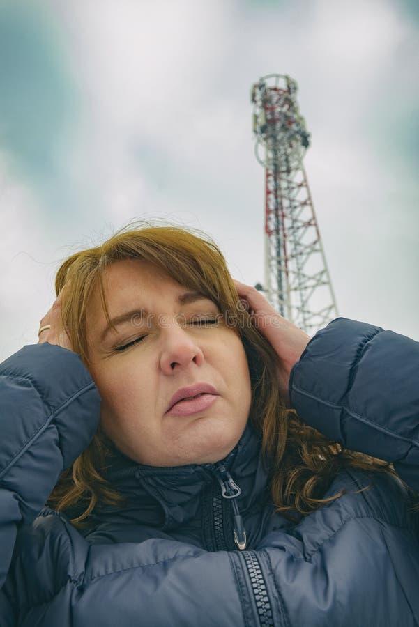La femme tient sa tête près du BTS image stock