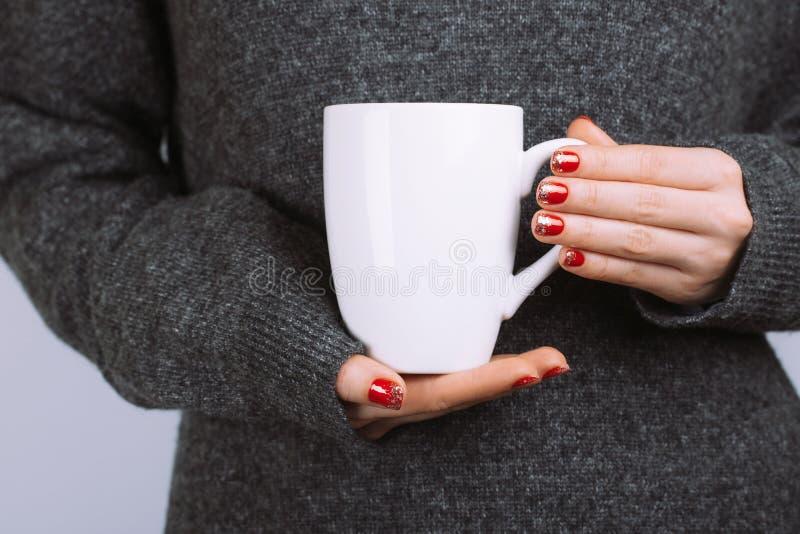 La femme tient la tasse de café blanc images stock