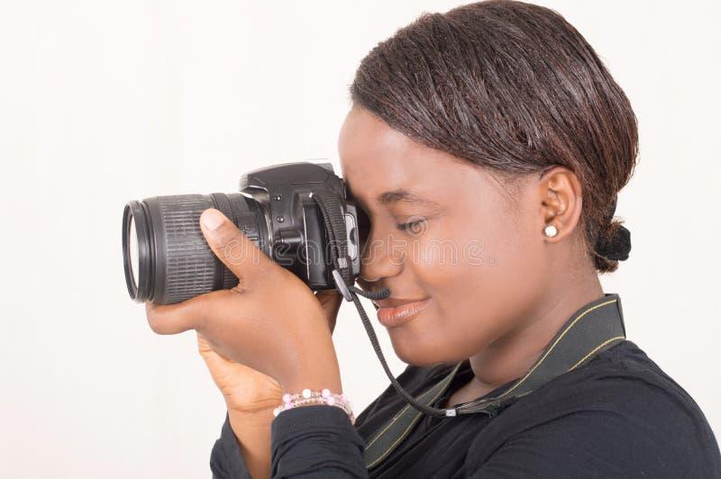 La femme tient un appareil photo numérique faisant des photos images stock