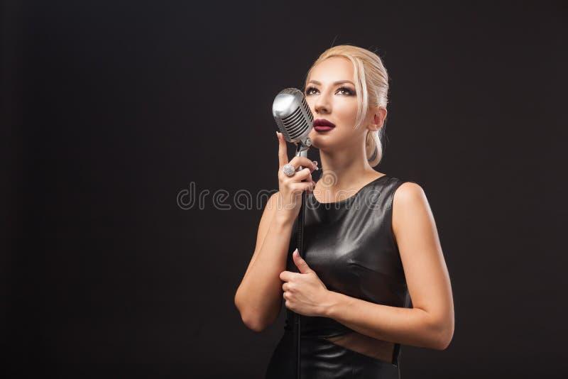 La femme tient un microphone en métal photo stock