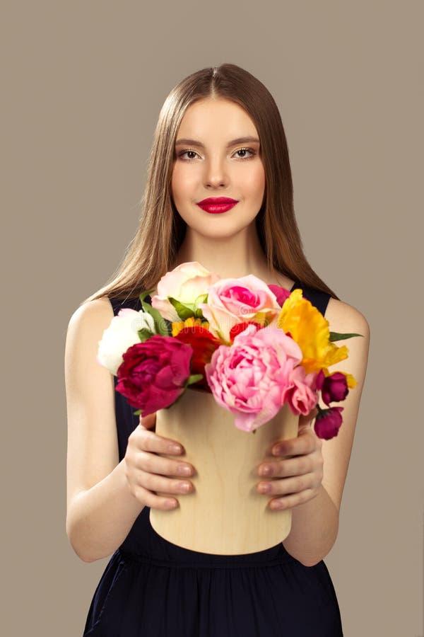La femme tient un panier avec des fleurs Fleurs de femme de mode photos libres de droits