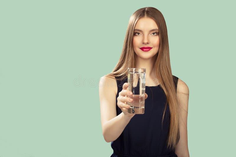 La femme tient un verre dans sa main Fond de turquoise image libre de droits