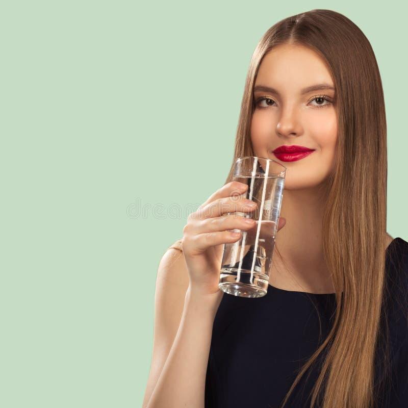 La femme tient un verre dans sa main Fond de turquoise photographie stock libre de droits