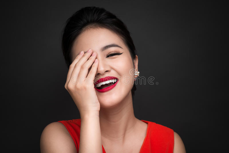 La femme timide de sourire a fermé son visage avec un backgro de noir de remise photo stock