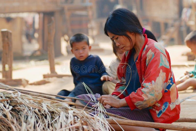 La femme tisse le détail de toit de paille en dehors de la maison dans un village pauvre près de Luang Prabang, Laos image libre de droits