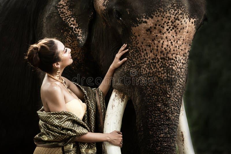La femme traditionnelle asiatique fait attention et étreint son éléphant de meilleur ami avec amour à la province de Kanchanaburi photo libre de droits