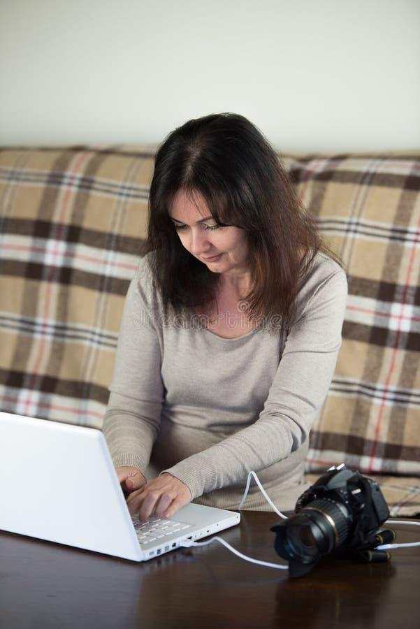 La femme transfère des images à partir de l'appareil-photo au PC d'ordinateur portable images stock