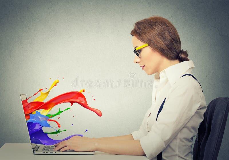 La femme travaillant sur l'ordinateur coloré éclabousse sortir de l'écran photos stock
