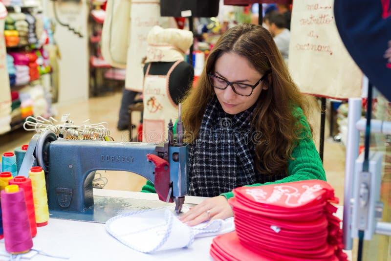La femme travaille à la machine à coudre dans la boutique de souvenirs photo libre de droits
