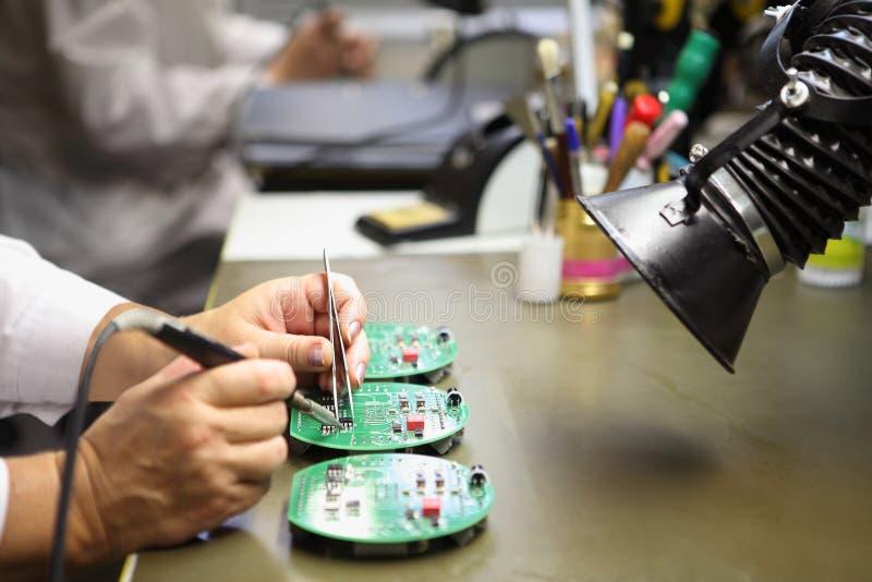 La femme travaille dans l'ensemble manuel du circuit imprimé électronique b images libres de droits
