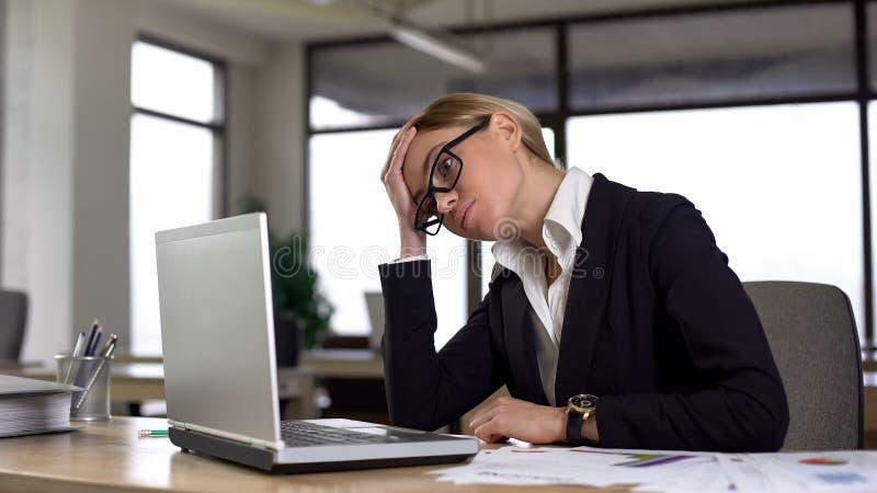 La femme triste regardant l'ordinateur portable, s'est inquiétée du projet difficile, manque d'expérience image libre de droits