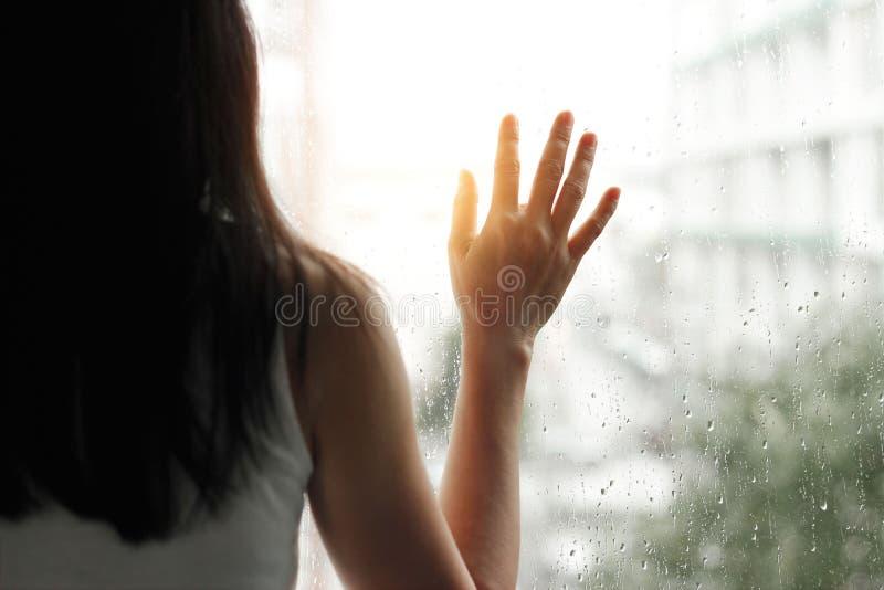 La femme triste regardant par le vitrail avec une pluie se laisse tomber photographie stock