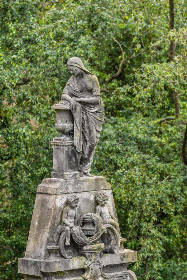 La femme triste se penche sur l'urne chez Glasgow Necropolis, Ecosse R-U photo stock