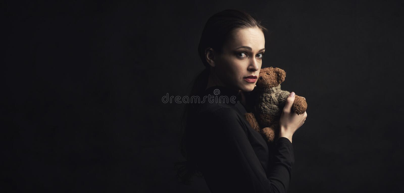 La femme triste tient un jouet d'ours de nounours photo stock