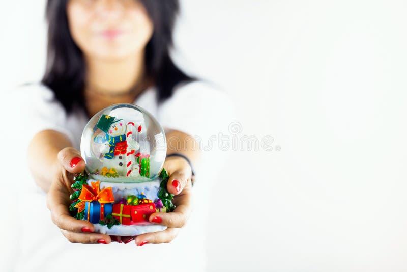 La femme trouble tient la sphère de bonhomme de neige photographie stock