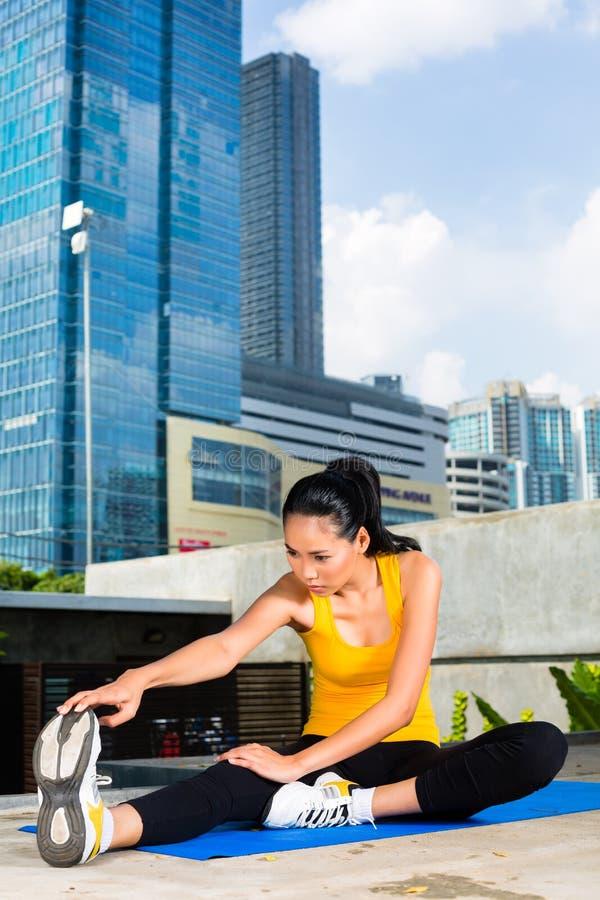 La femme urbaine folâtre - la forme physique dans la ville asiatique image libre de droits