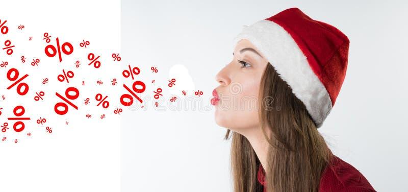La femme utilisant le chapeau rouge du père noël souffle des pourcentages de remise photos stock