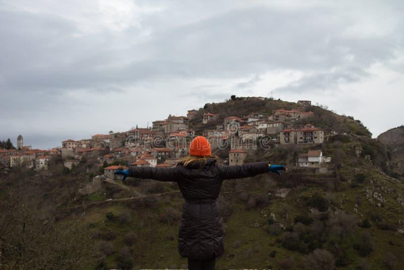 La femme utilisant un chapeau orange se tient avec les mains grandes ouvertes devant le village grec Vytina, pendant un hiver fro photo stock