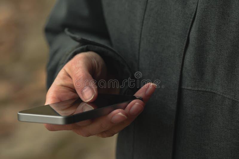 La femme utilise le smartphone sur la rue en hiver photos stock