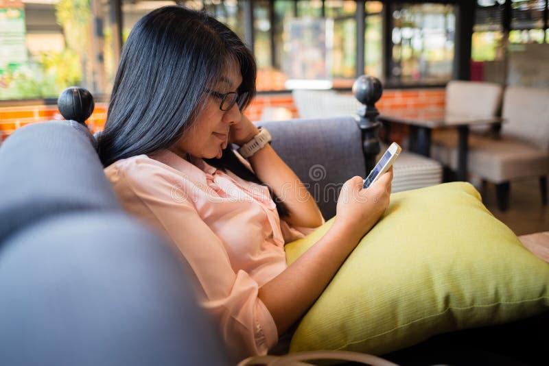 La femme utilisent le téléphone en café photos libres de droits