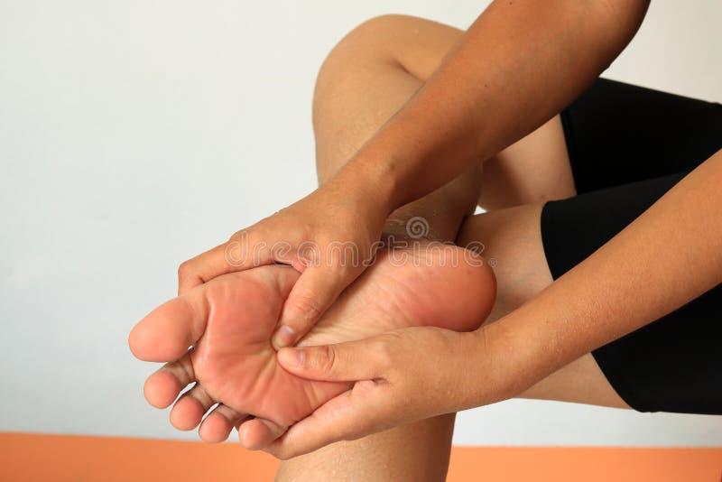 La femme vérifie son pied douloureux photos libres de droits