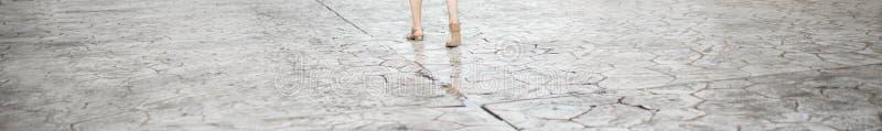 La femme va sur la rue Culture de jambes Texture de la vieille route avec des fissures Surface d'asphalte sur la rue Drapeau de W photographie stock