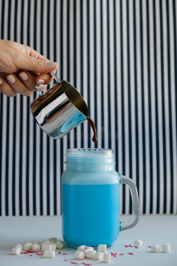 La femme verse le café dans la tasse de lait bleu coloré sur un fond noir et blanc Lait de poule, cocktaill, frappuccino Licorne  image stock