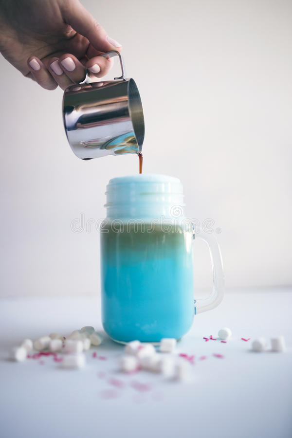 La femme verse le café dans la tasse stylisée de pot de maçon de lait bleu coloré Lait de poule, cocktaill, frappuccino Café de l photos libres de droits