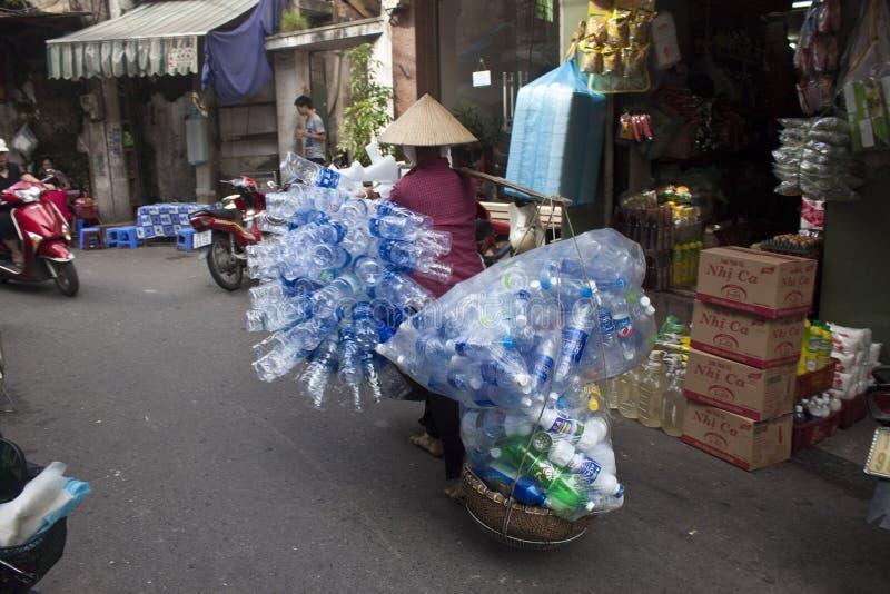 La femme vietnamienne porte de vieilles bouteilles en plastique photo stock