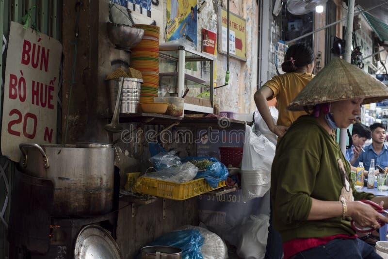 La femme vietnamienne prépare la nourriture à un magasin de soupe à rue en Ho Chi Minh City, Vietnam image libre de droits