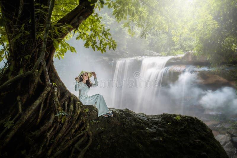 La femme vietnamienne s'assied sous un bel arbre de cascade avec a photos stock