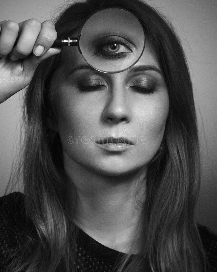 La femme voient par le troisième oeil par le verre de loupe Rebecca 36 photos stock