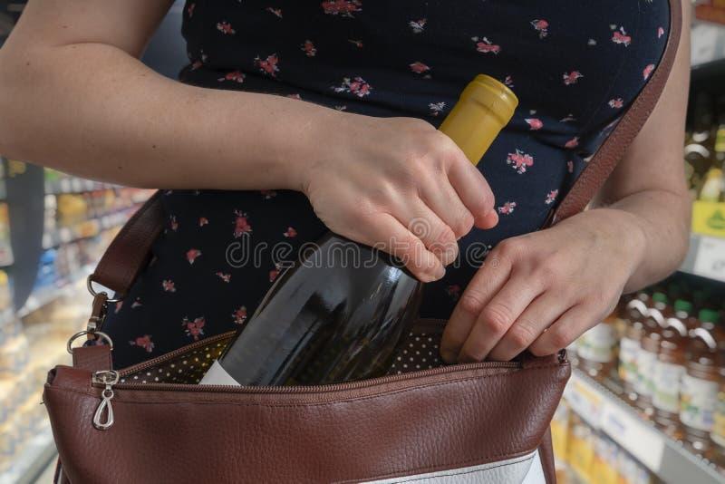 La femme vole la bouteille de vin et la cache dans le sac à main dans le supermarché photo libre de droits