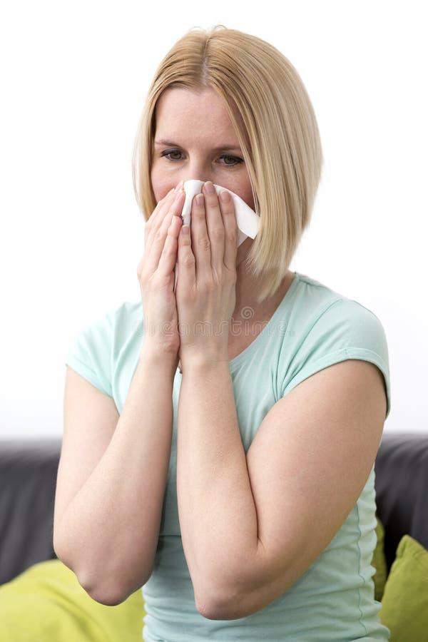 La femmina allergica, soffia il suo naso immagini stock