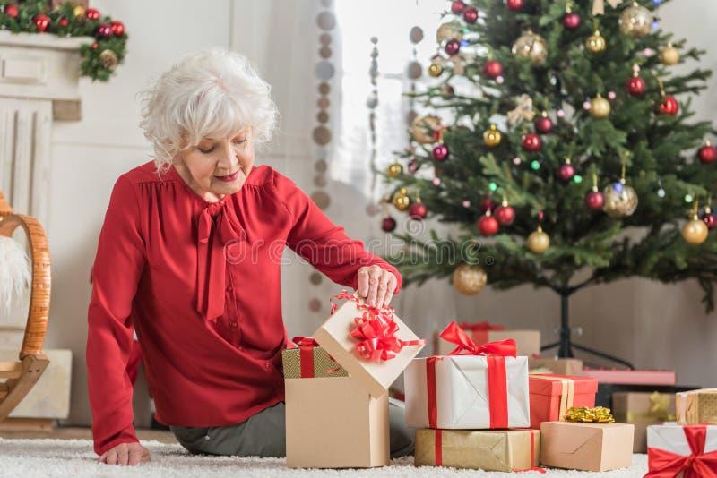 La femmina anziana allegra sta riposando nella sua casa alla festa immagini stock