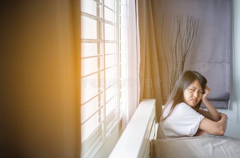 La femmina asiatica fa svegliare un'emicrania sulla camera da letto dopo di mattina fotografia stock