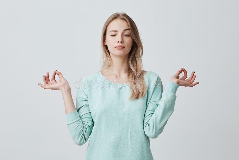 La femmina attraente concentrata con capelli tinti lunghi dressen nei supporti blu nella posa del loto, medita e gode di pacifico fotografie stock