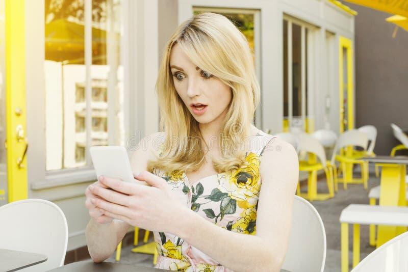 La femmina bianca con capelli biondi ha un'espressione colpita mentre esamina il suo telefono cellulare fotografia stock