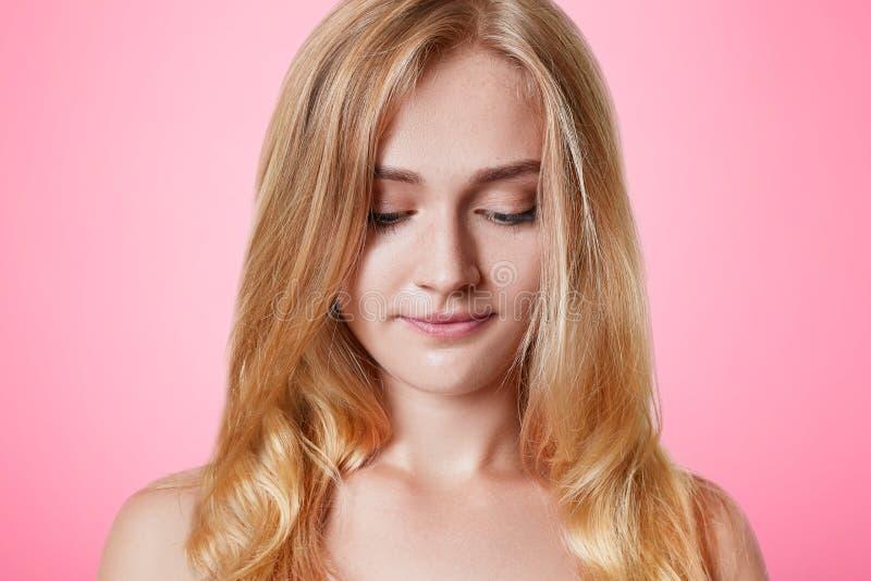 La femmina bionda seria con il apearance supplichevole guarda giù, ha espressione timida, isolata sopra fondo rosa Belli giovani  fotografia stock