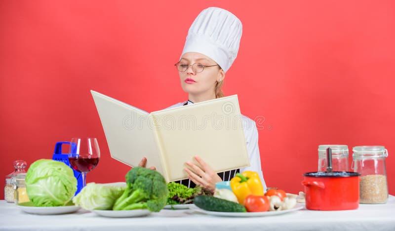 La femmina in cappello ed in grembiule conosce tutto circa le arti culinarie Esperto culinario Cuoco unico della donna che cucina fotografia stock