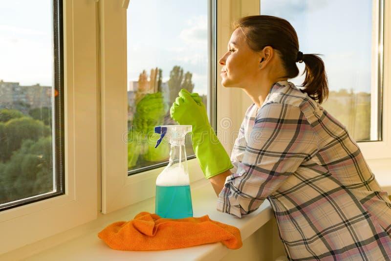 La femmina con il detersivo di gomma dei guanti protettivi, dello straccio e dello spruzzatore esamina una finestra lavata pulita immagini stock libere da diritti