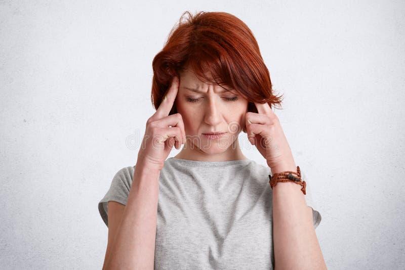La femmina concentrata dai capelli rossi pensierosa tiene le dita sulle tempie, prove per ricordare qualcosa in mente, messa a fu immagini stock