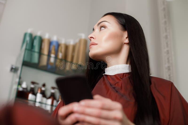 La femmina di calma sta uccidendo il tempo con lo smartphone in salone fotografia stock libera da diritti