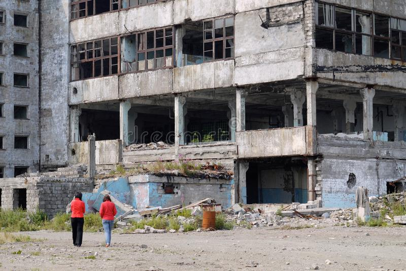 La femmina due dipende i precedenti di un grattacielo abbandonato fotografia stock libera da diritti