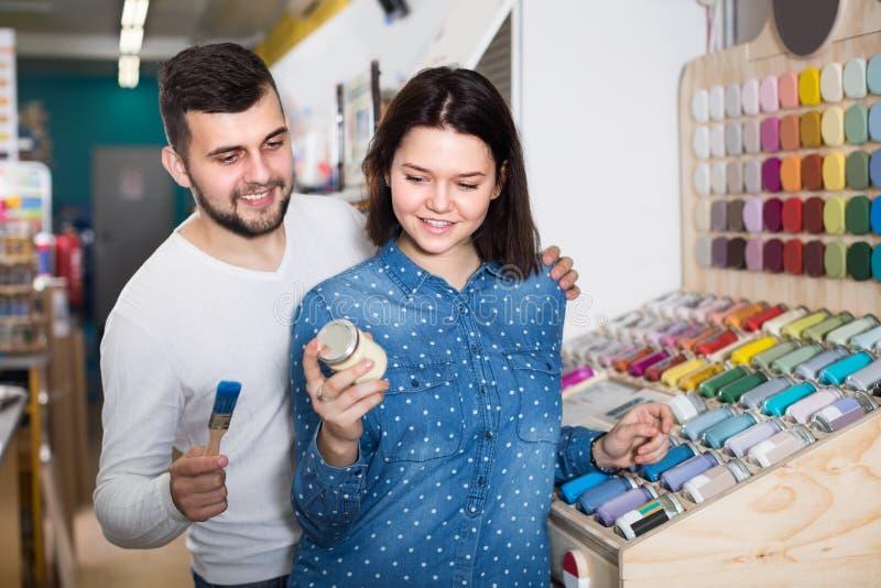 La femmina ed il maschio stanno decidendo dei materiali per la decorazione della casa immagini stock libere da diritti