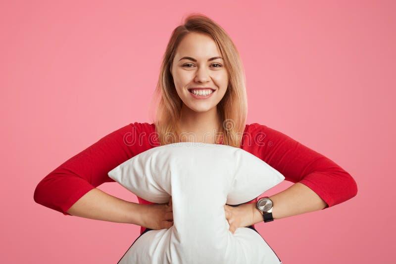 La femmina felice tiene il cuscino, ha sogno sano, felice di cominciare il nuovo giorno, porta il maglione rosso, posa contro il  fotografia stock libera da diritti