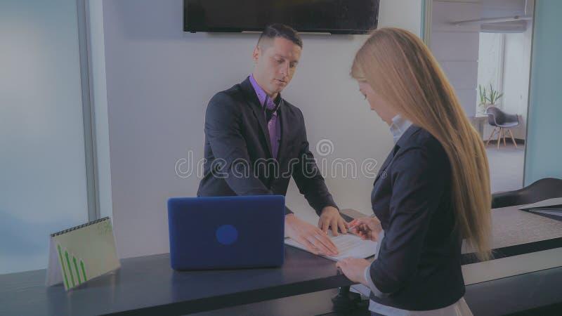 La femmina firma il trattato in banca fotografia stock