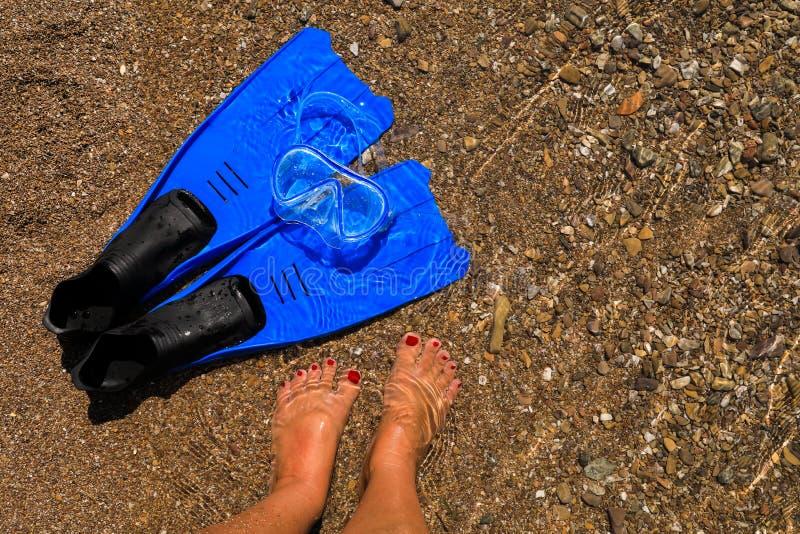 La femmina ha abbronzato le gambe, le alette e la maschera sulla spiaggia, concetto di vacanza del mare immagini stock libere da diritti