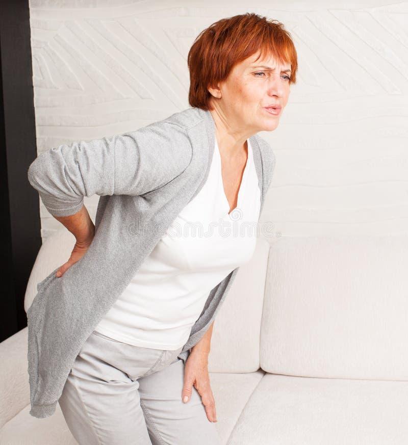 La femmina matura ha parte posteriore di dolore dentro immagini stock libere da diritti